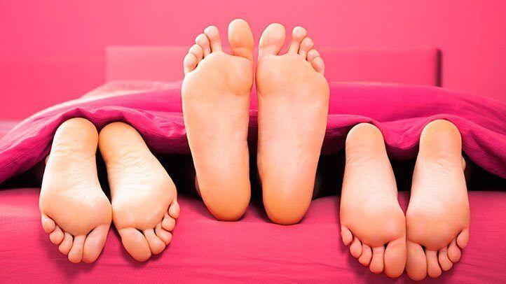 trei seturi de picioare într-un pat